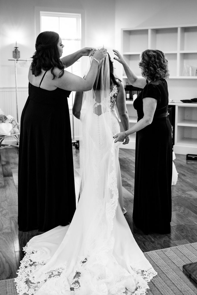 A mother and sister help the bride with her veil