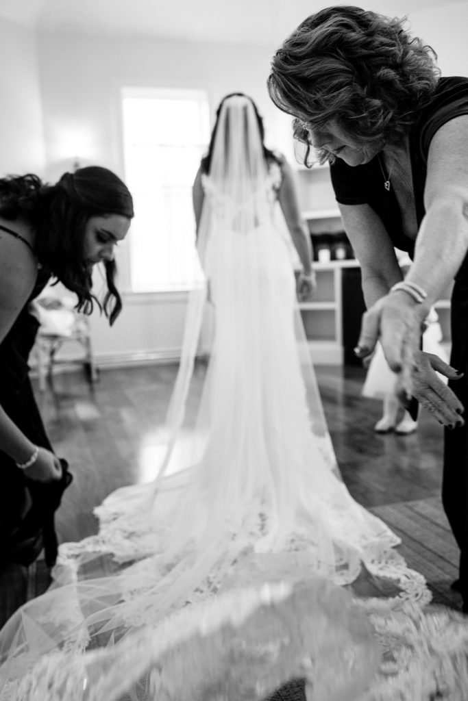 A mother and sister help fluff the brides veil