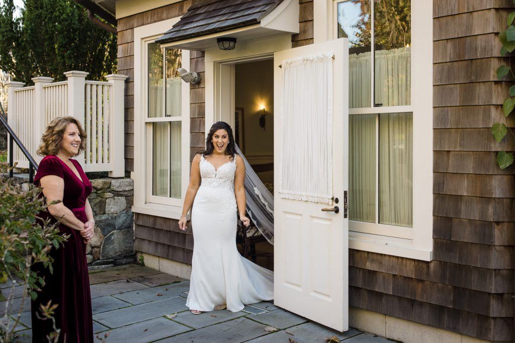 A bride walks out the door smiling to see her father