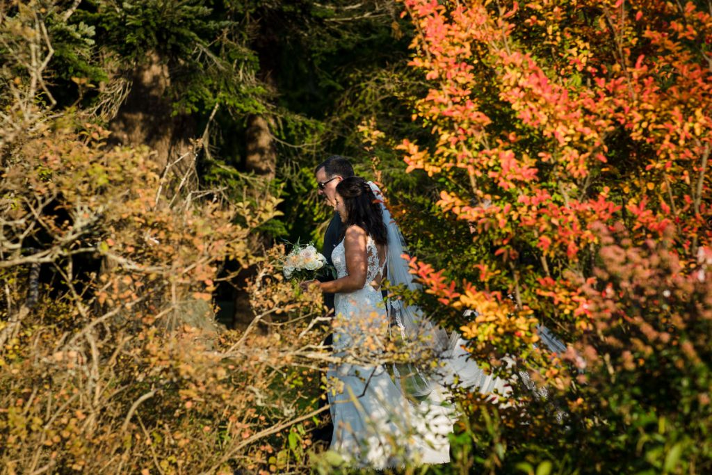 A glimpse of a bride and her father processing past fall trees