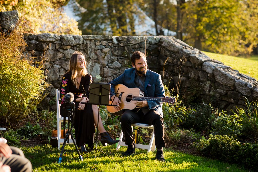 A man and woman sing and play guitar at a garden wedding