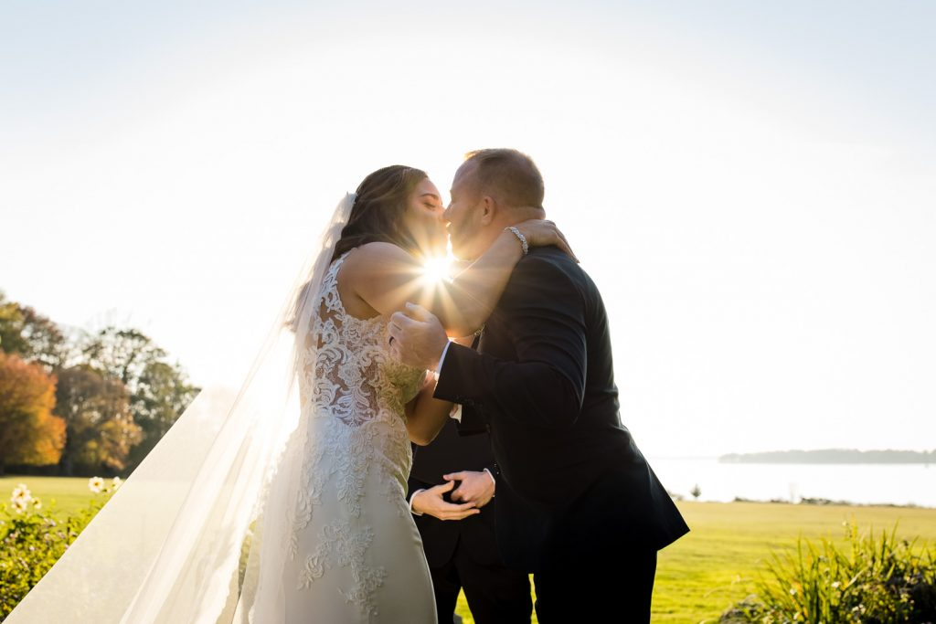 A bride and groom kiss at the end of their wedding ceremony