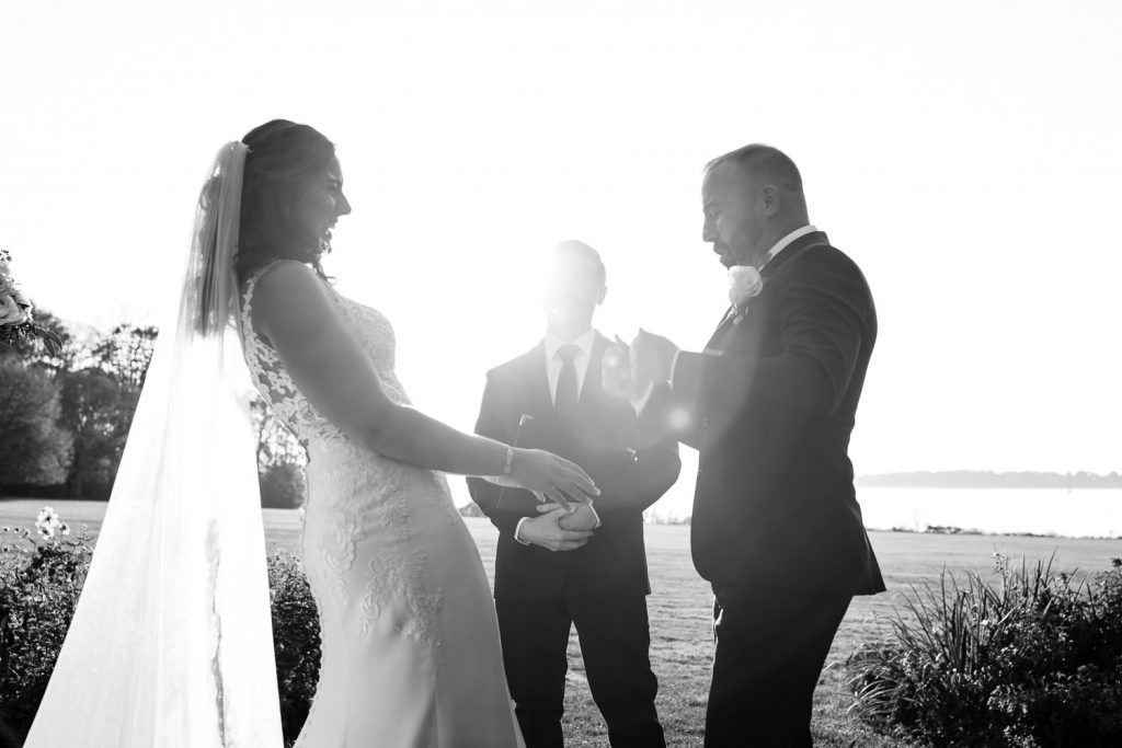A backlit bride and groom laugh and celebrate after being pronounced husband and wife