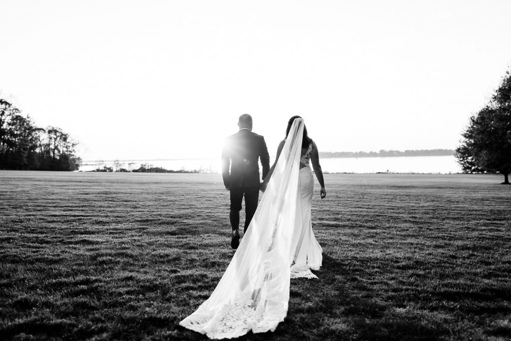 A groom and bride with a cathedral veil walk towards the ocean in bristol, ri