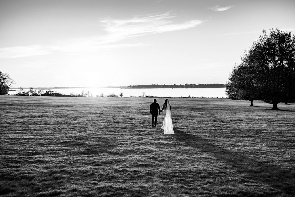 A bride and groom walk away towards the ocean on a great lawn