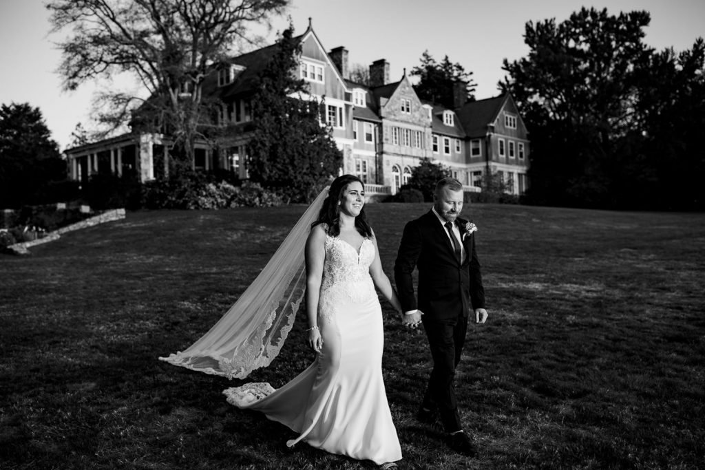A black and white photo of a bride and groom walking hand in hand in front of blithewold mansion after their wedding