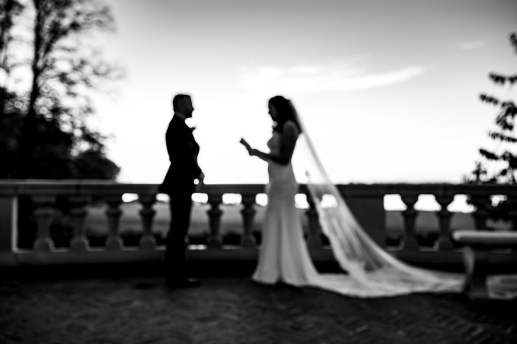 An out of focus silhouette photo of a bride reading vows to her groom