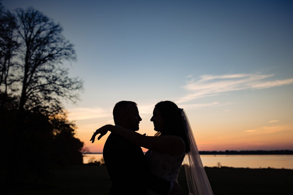 A bride and groom in silhouette in front of a beautiful sunset at their blithewold mansion wedding