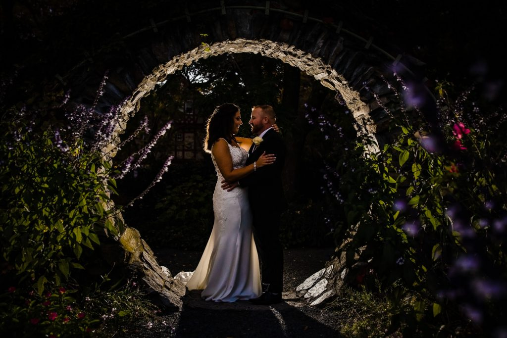 Bride and groom stand inside a moon gate at blithewold mansion rose garden at night