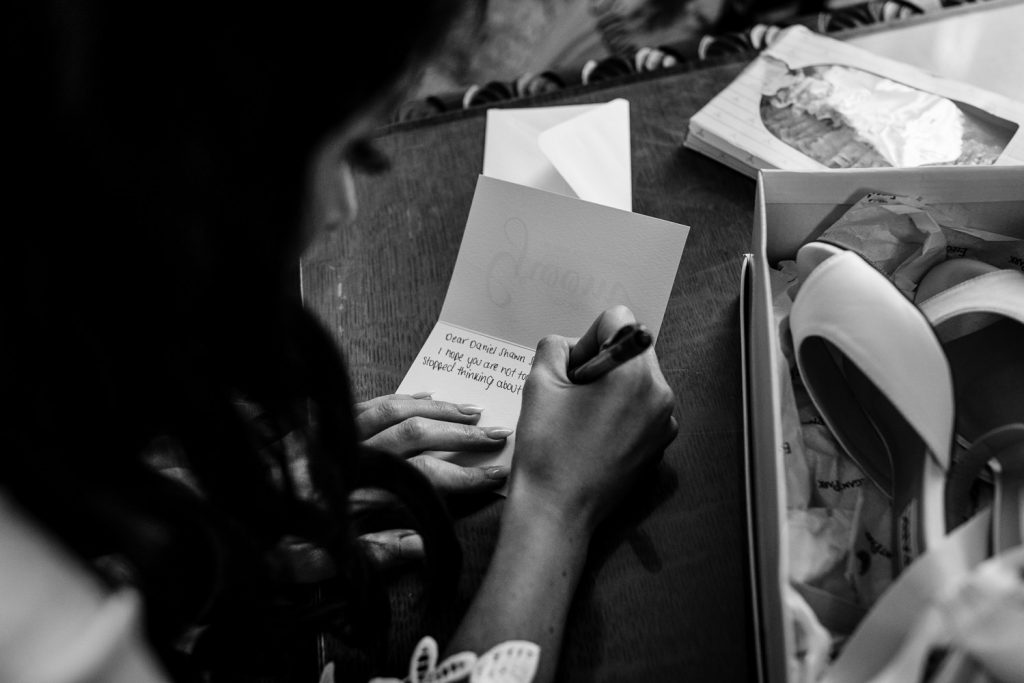 A bride writing a letter to her groom on their wedding day