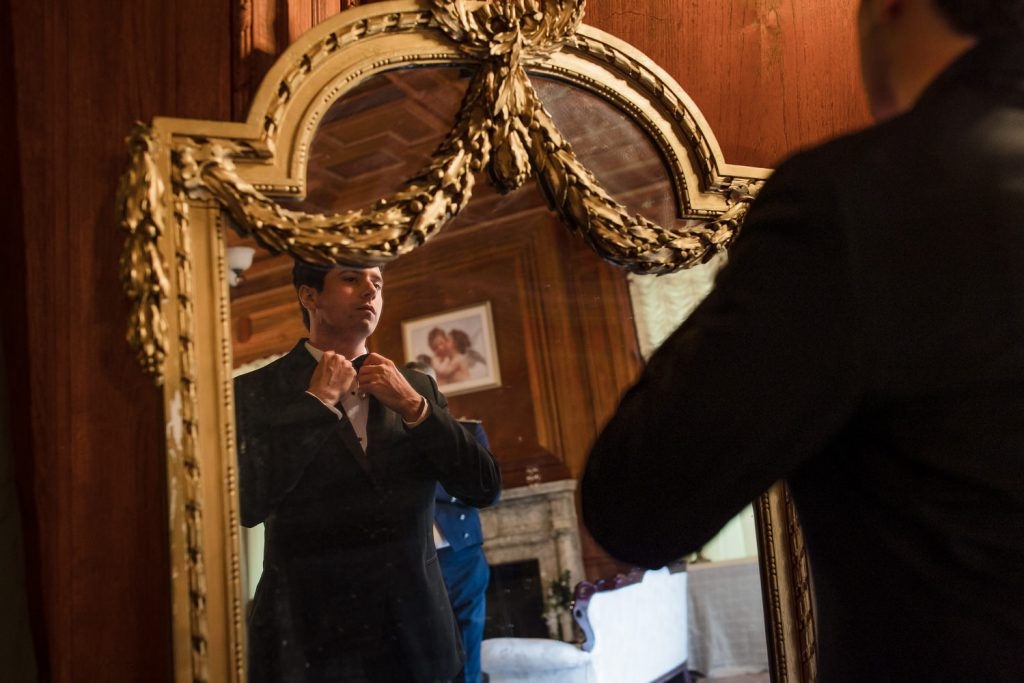 A groom adjusts his bowtie in front of a gilded gold mirror