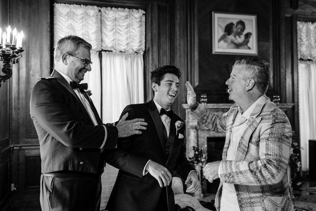 Two men joke and kid around with a groom wearing a tuxedo