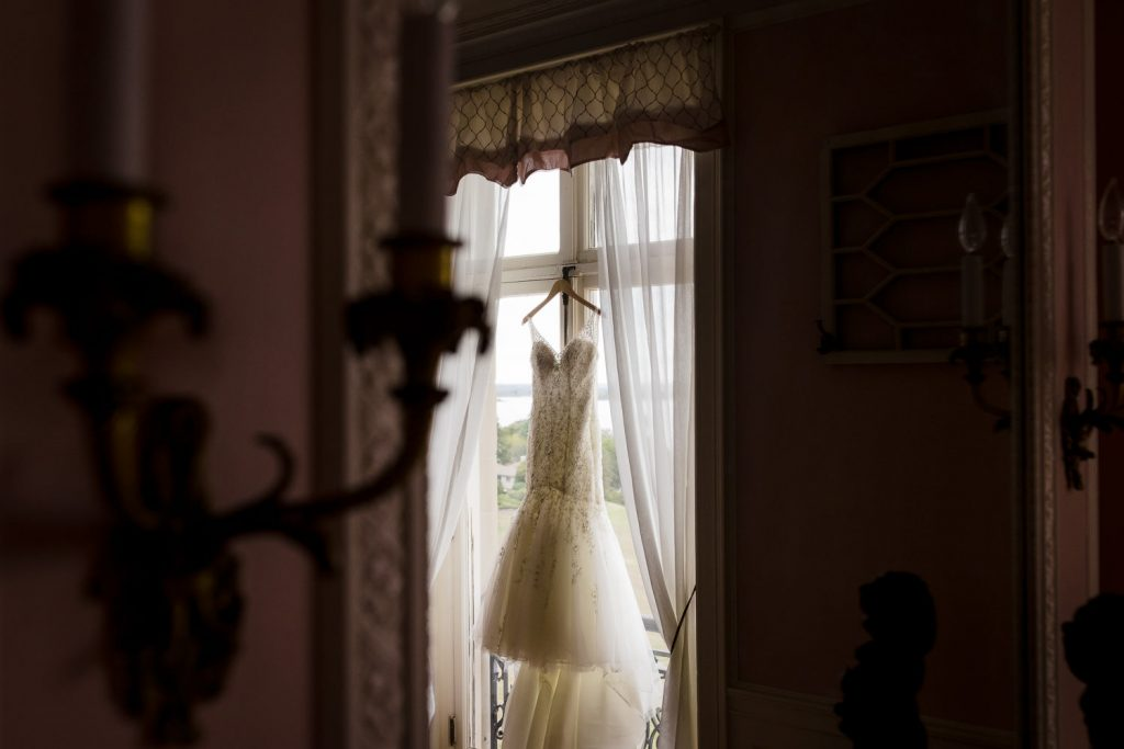 A wedding gown hanging in the window of a mansion reflected in an antique mirror