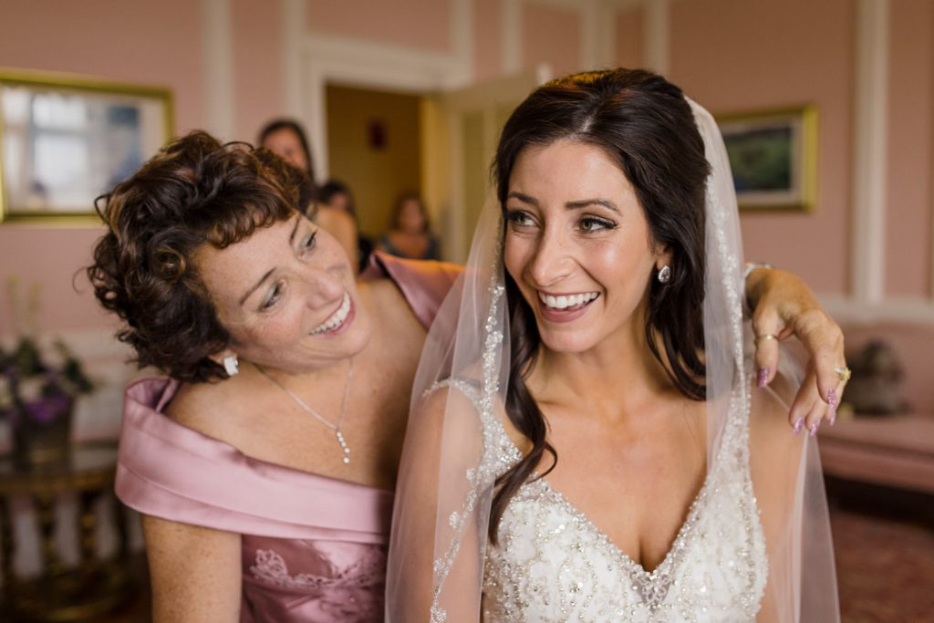 A bride and her mother smile at each other as she helps her put her veil on