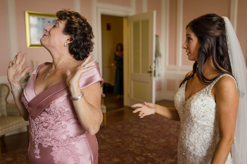 A bride watches as her mother walks away with hands in the air trying not to cry