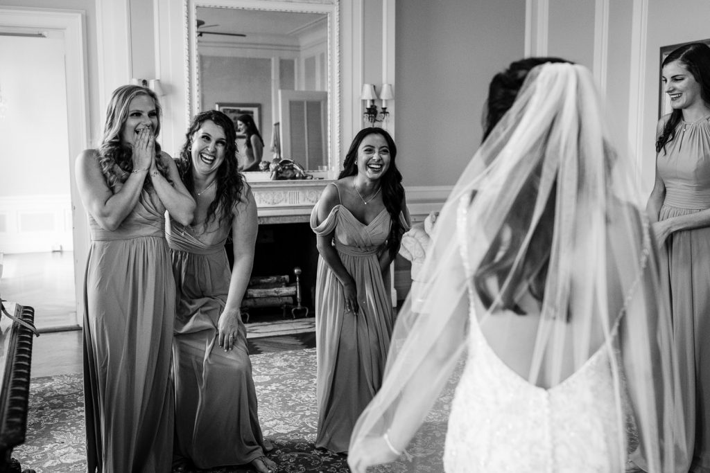 Four bridesmaids smile, laugh and gasp as they see their friend the bride dressed in her gown