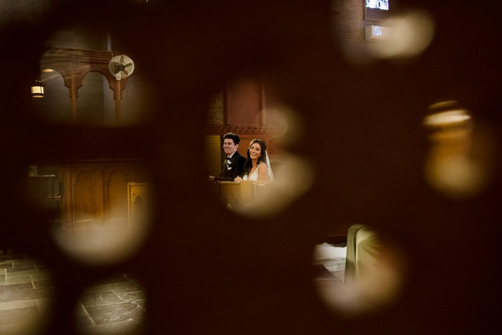 A bride and groom kneel at the alter of their wedding as seen through a wood screen