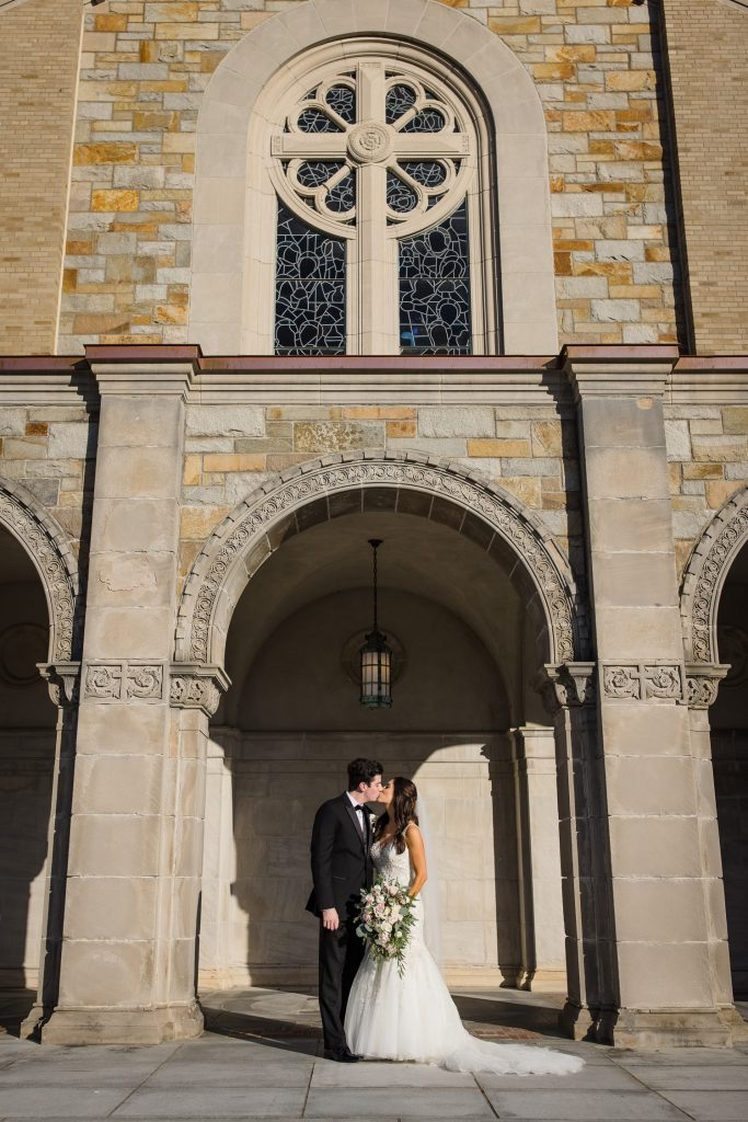 A bride and groom kiss beneath an archway in front of the aldrich mansion chapel