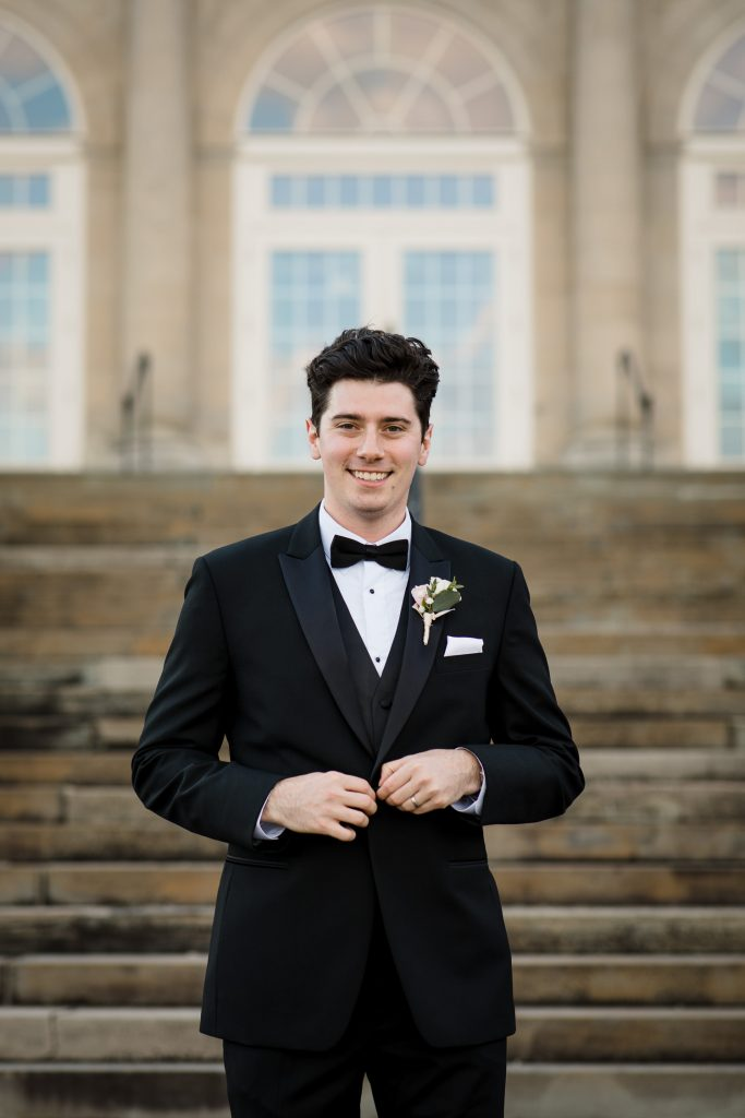 A groom portrait on the steps of the aldrich mansion