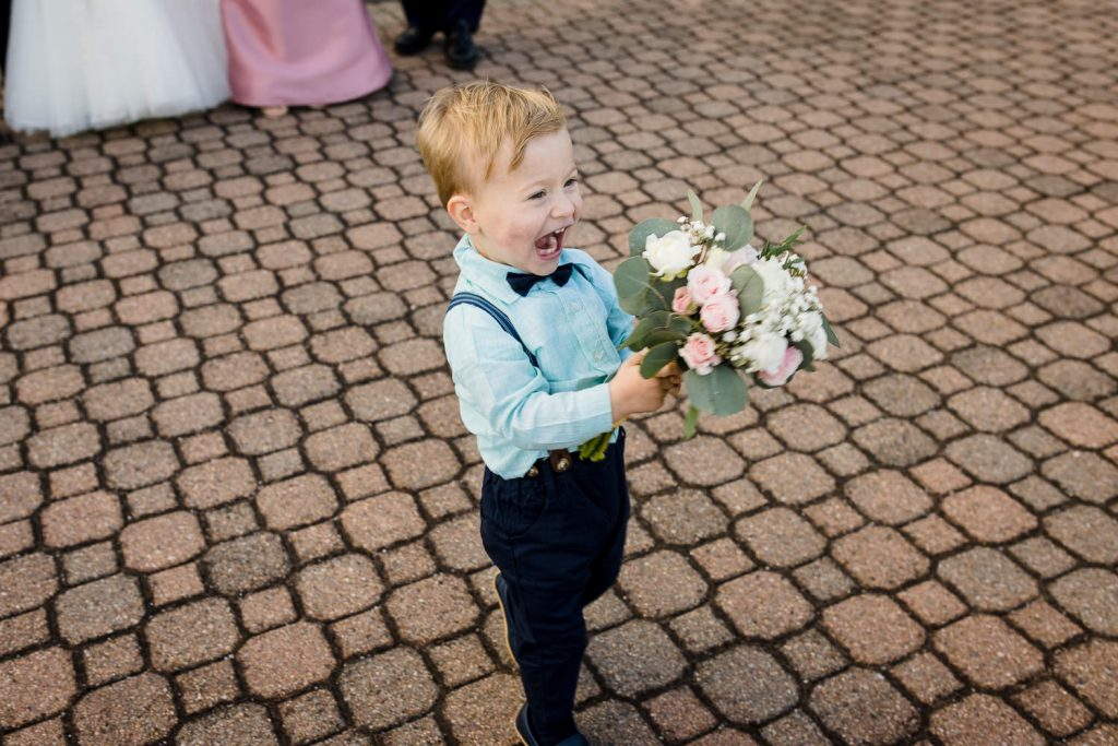 A toddler boy in suspenders laughs emphatically as he walks away from adults holding a bridal bouquet