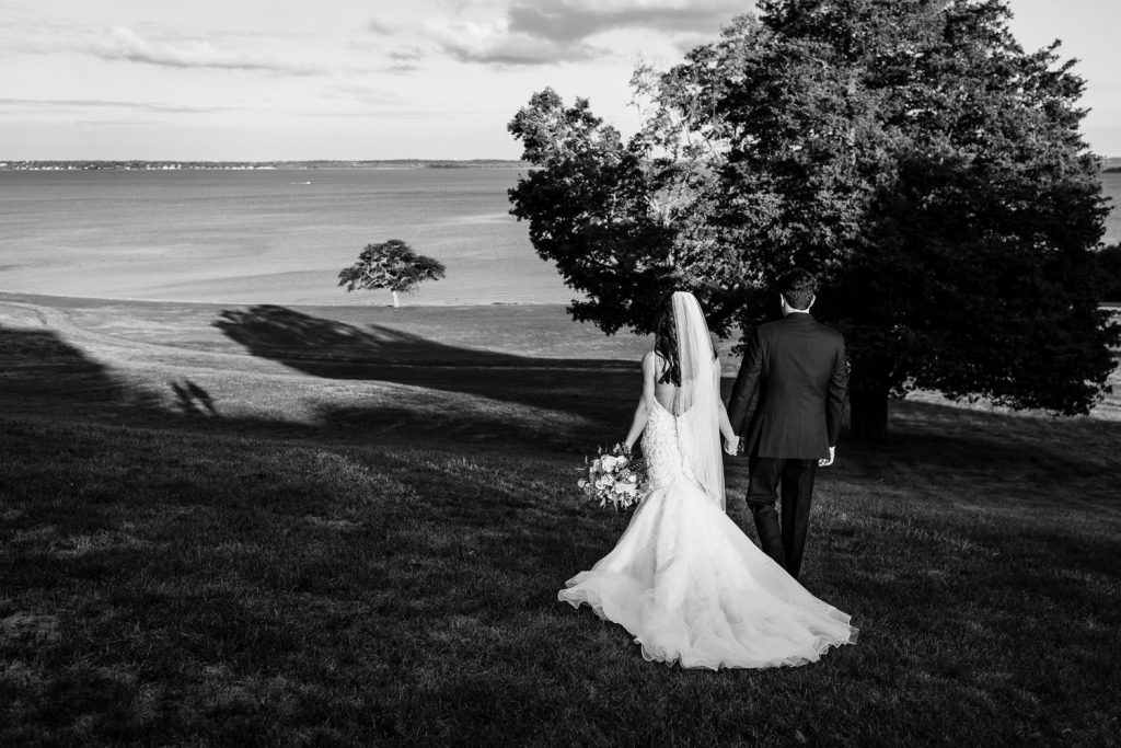 A bride and groom walk down a grassy slope to the water at their aldrich mansion wedding