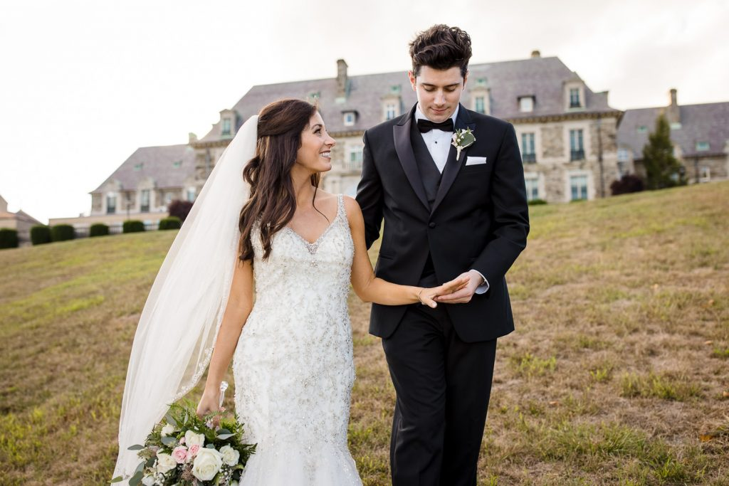 A groom holds his brides hand and checks out her ring as they walk away from the aldrich mansion