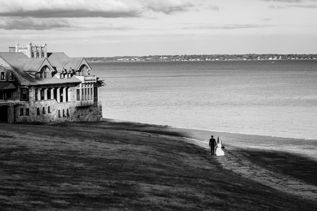 A bride and groom walking off in the distance by the water and boathouse at the aldrich mansion in warwick