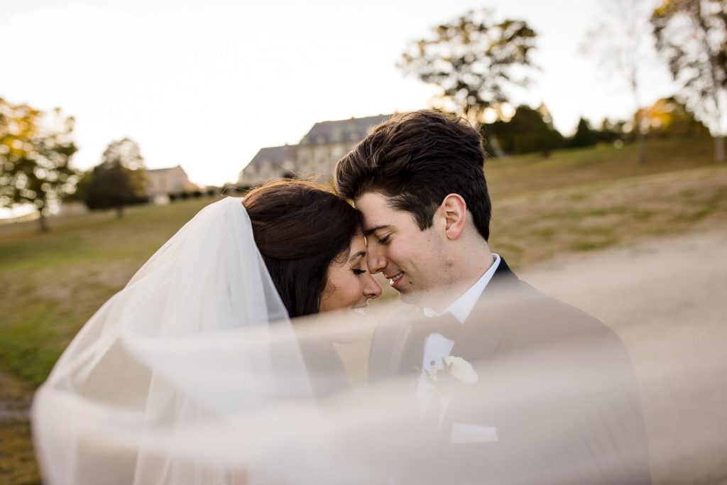 A bride and groom touch foreheads as the brides veil blows in the breeze