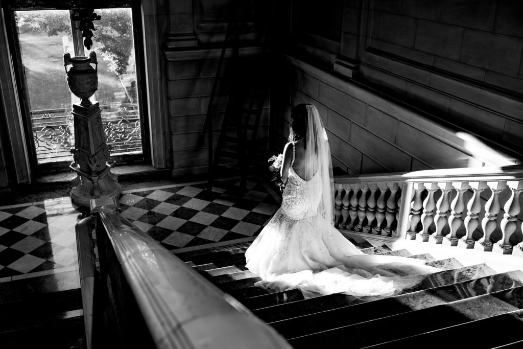 A ray of sunlight illuminates a bride walking down the marble staircase at the aldrich mansion to her wedding ceremony