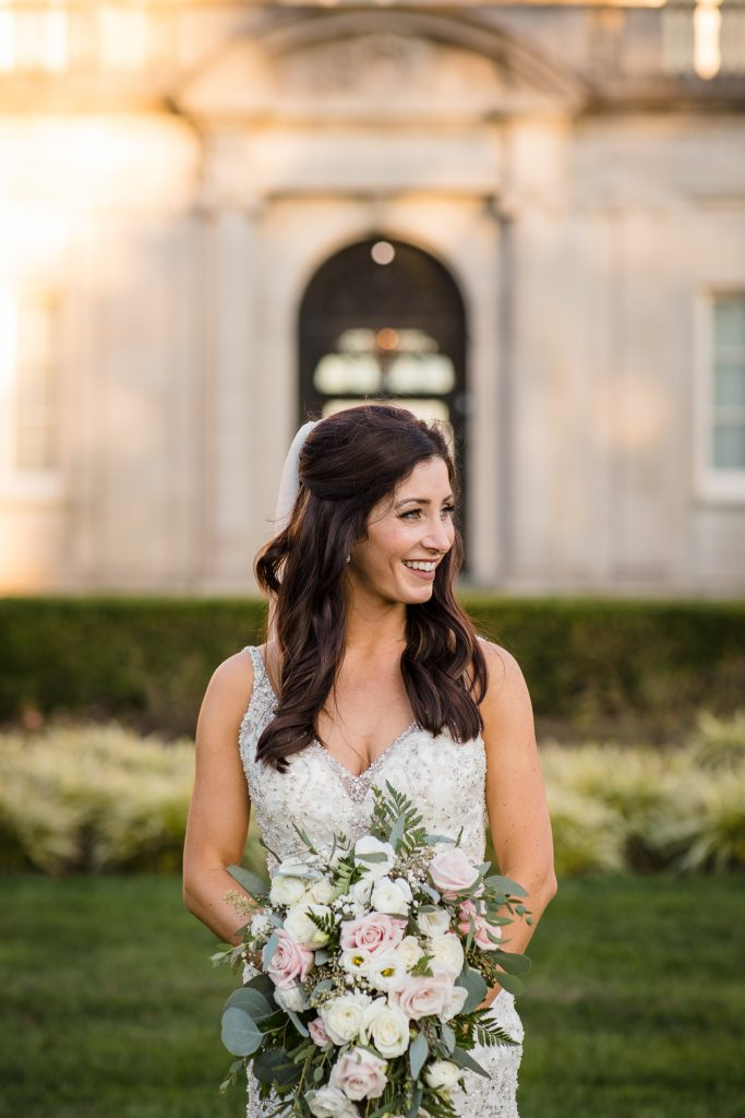 A bride smiles and holds her wedding bouquet in front of a mansion