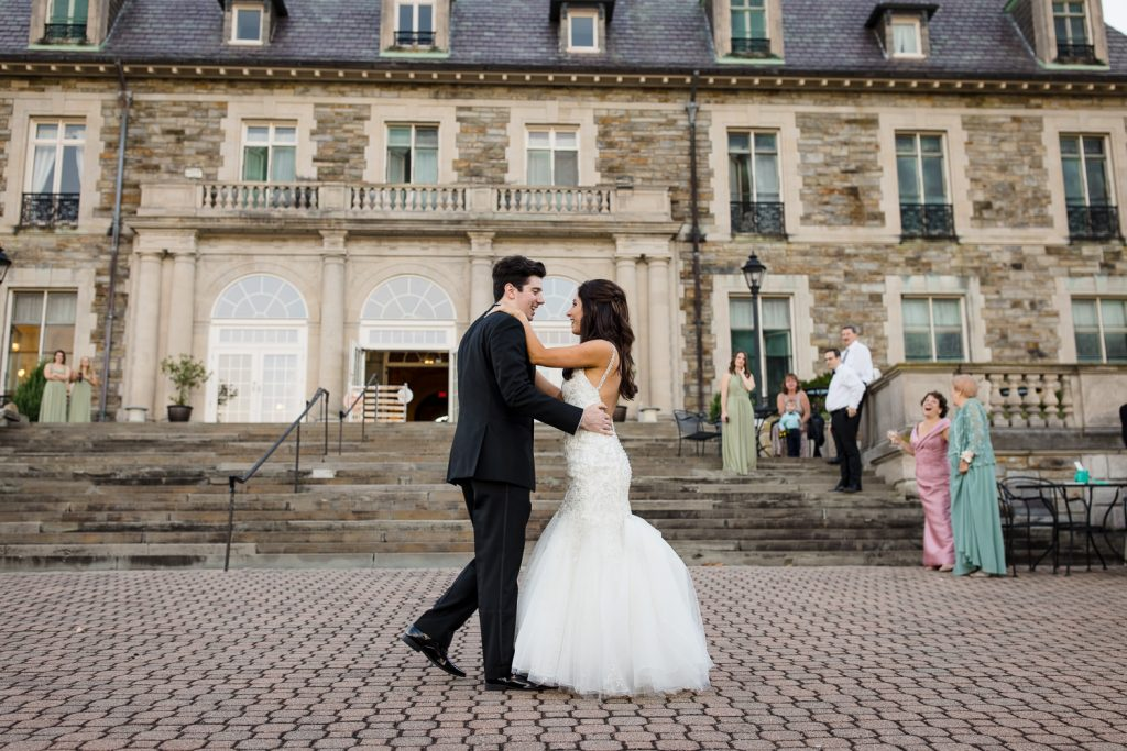 A bride and groom dance on an outdoor patio in front of a mansion