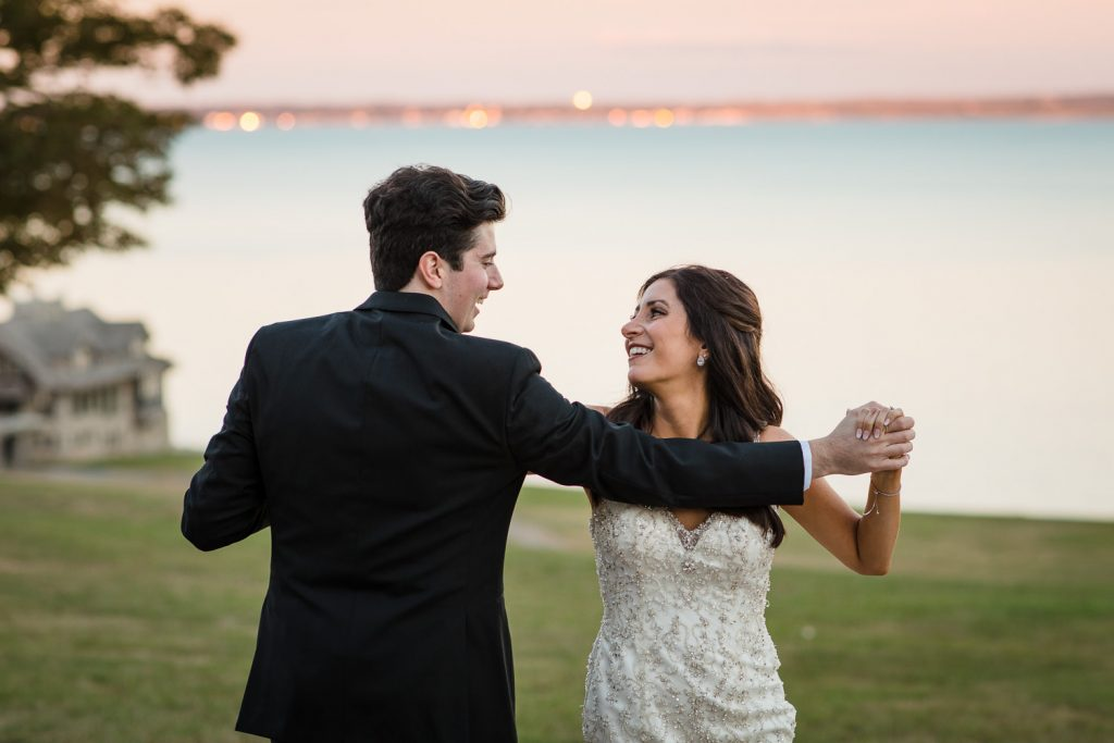 A bride and groom do a choreographed first dance with a sunset and sea view in the background