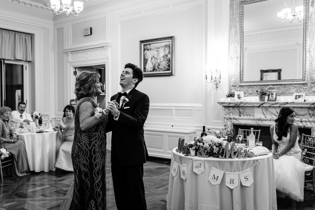A mother and her son dance as the bride sits at the sweetheart table