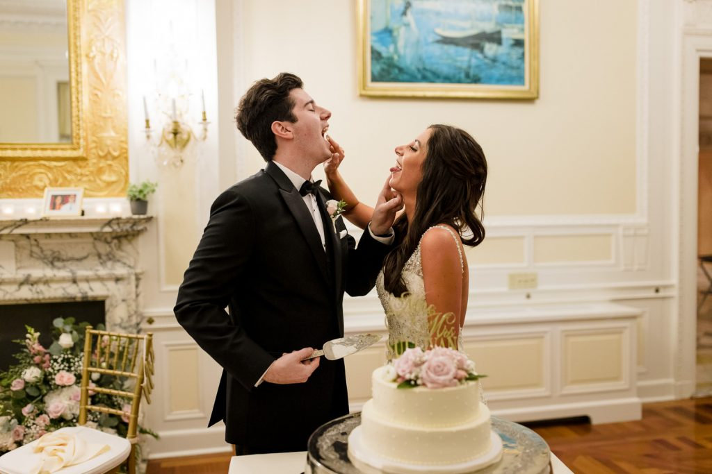 A bride and groom both shove cake in each others mouths at the same time
