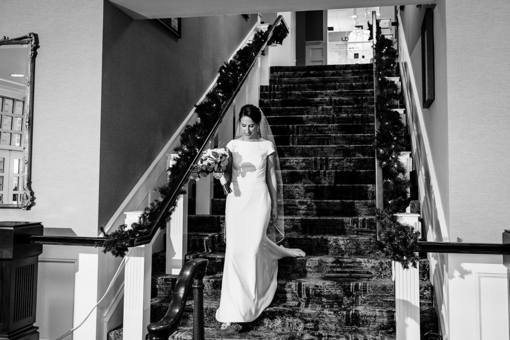 A bride walks down the stairs to her wedding first look at hotel viking in newport ri