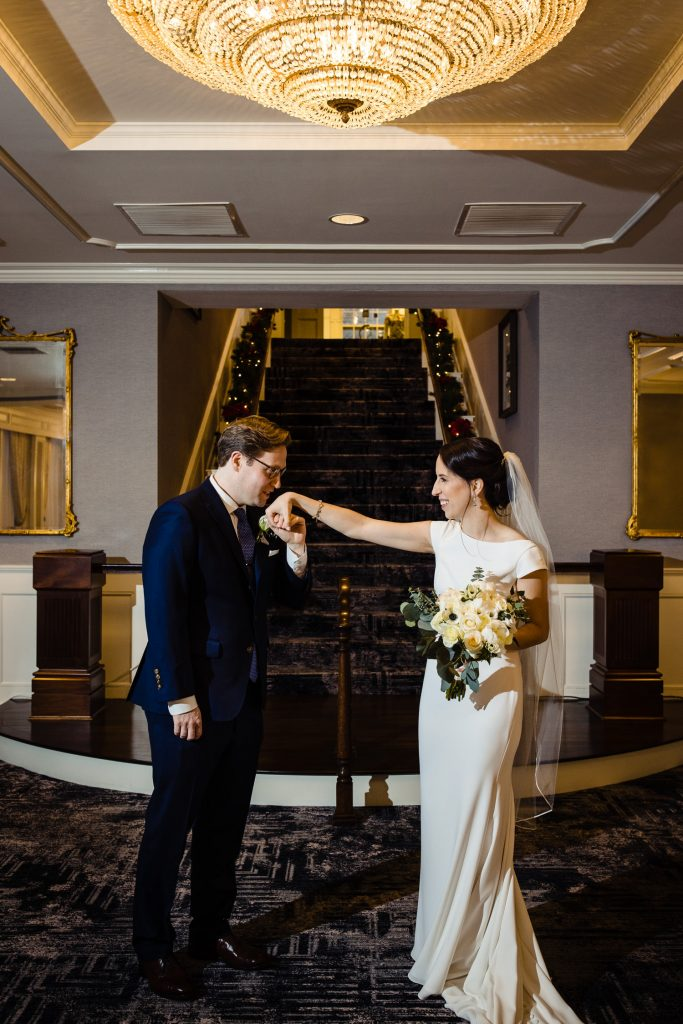 The groom kisses the hand of his bride at the base of the hotel viking staircase beneath a beautiful chandelier at their wedding