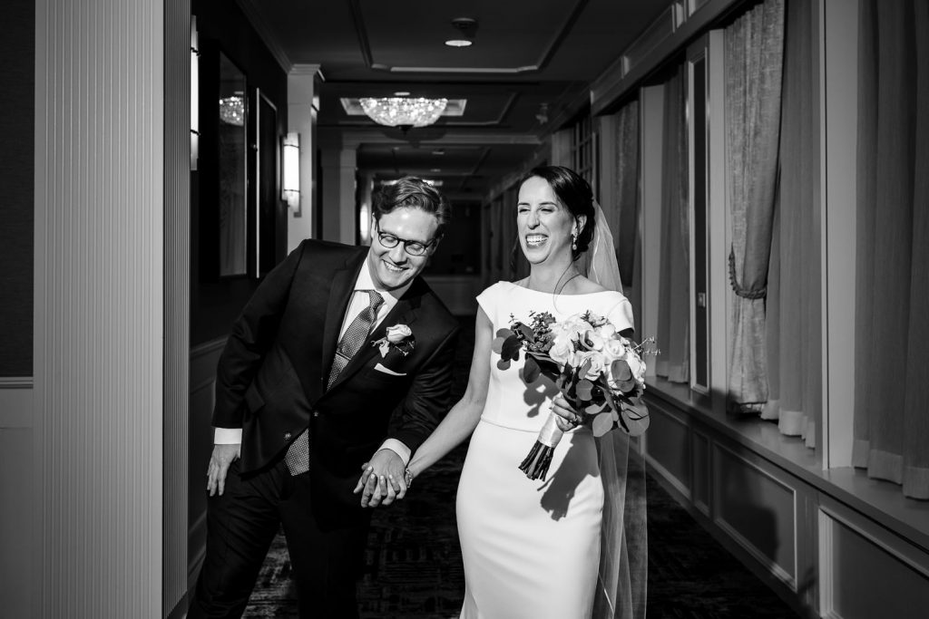 A bride and groom walk hand and hand and laugh