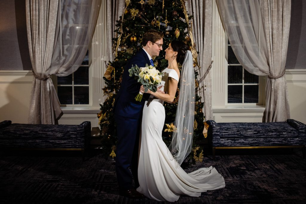 The groom dips his bride in front of the christmas tree at Hotel Viking before their wedding