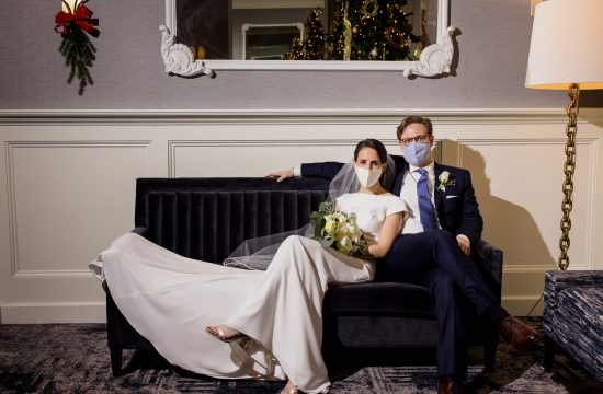 A 2020 bride and groom pose for wedding photos on a velvet couch wearing face masks