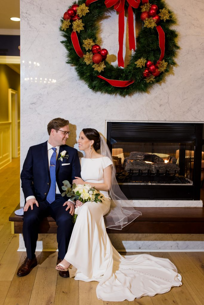 A bride and groom sitting by the fireplace in the lobby at hotel viking before their wedding