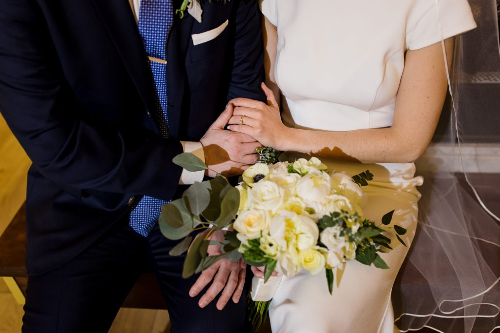 A groom holds his bride's hand that is on his arm