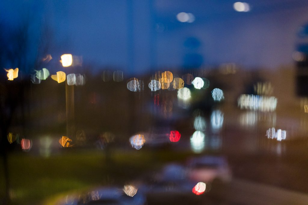Street lights bokeh as seen through a rainy covered window at night