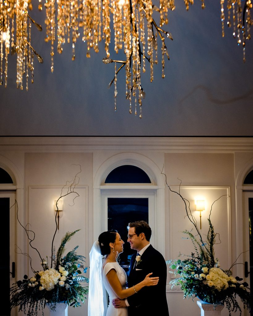 A bride and groom embrace under the beautiful chandelier at their Queen Anne's Loft wedding