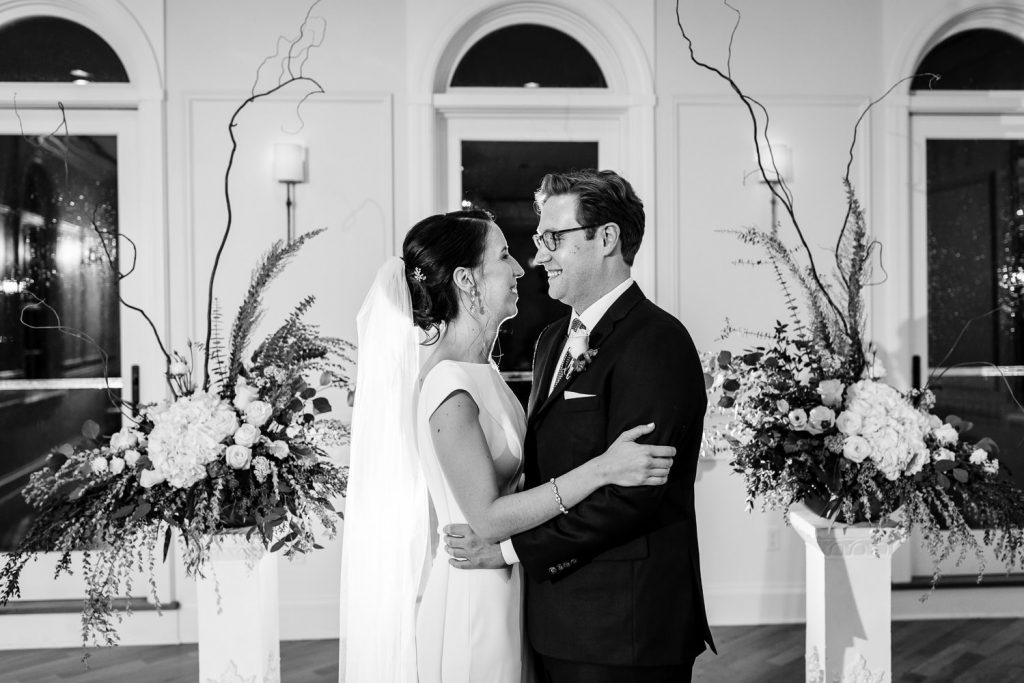 A black and white photo of a bride and groom looking into each others eyese