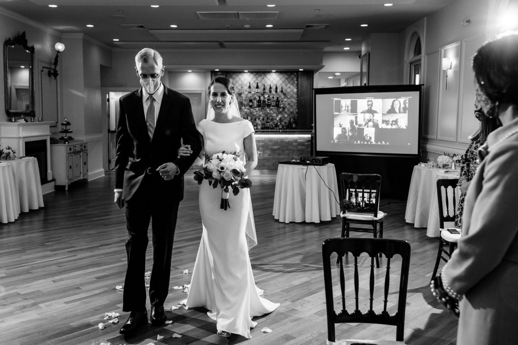 A bride's father wearing a face mask escorts his daughter down the aisle of her wedding with a projector screen and virtual guests in the background
