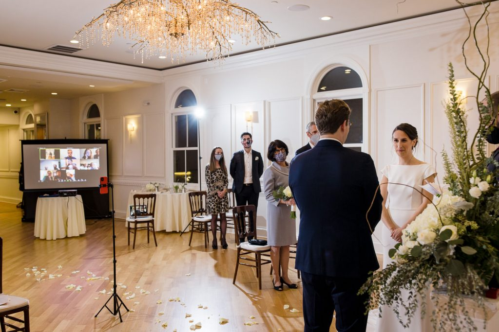 A bride and groom stand at the front of the room with a few guests in person and more on a projector screen watching the ceremony