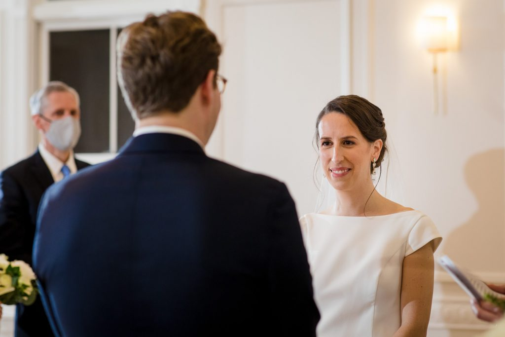 A bride smiles as her groom reads his vows