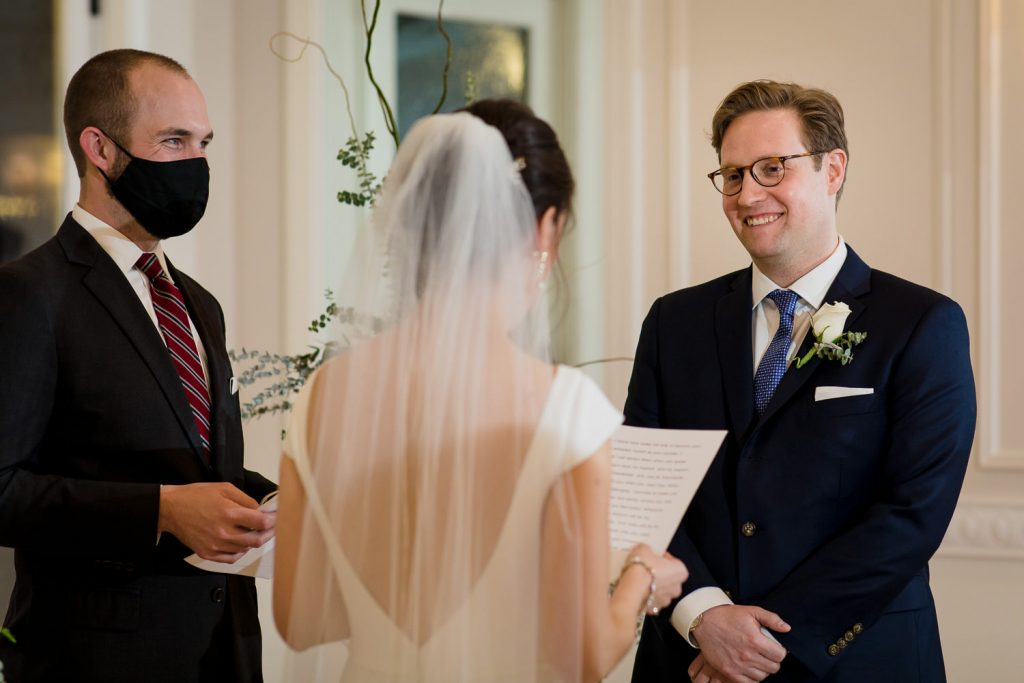 A groom smiles as his bride reads her wedding vows of a piece of paper