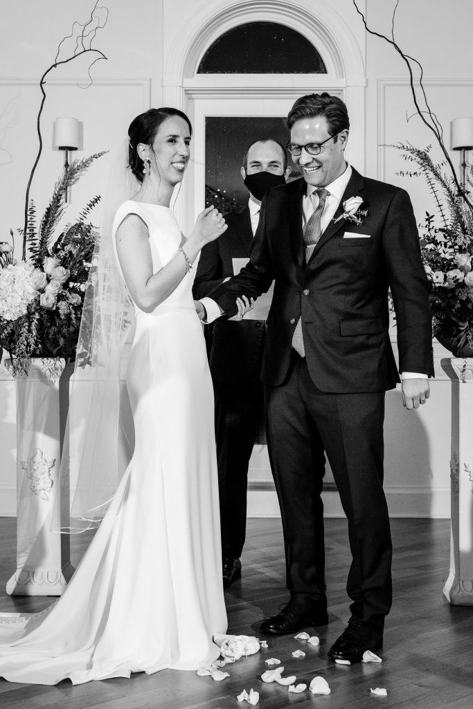 A bride and groom smile as the groom breaks the glass during the jewish wedding ceremony.