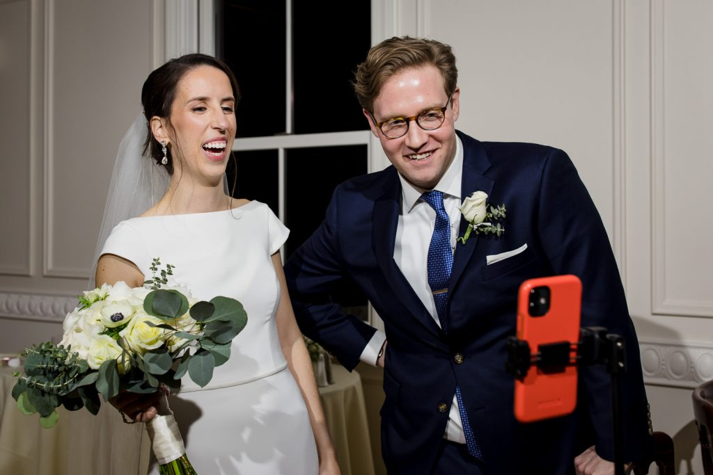 A 2020 bride and groom laugh as they see their virtual wedding guests on a phone screen.